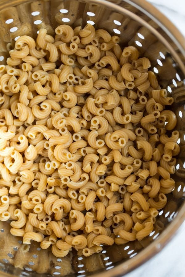 A colander of cooked elbow macaroni for Shrimp Pasta Salad