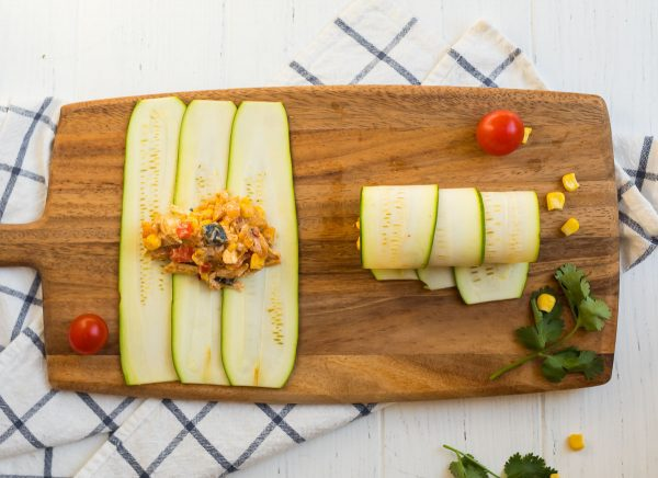 Rolling up Zucchini Enchiladas