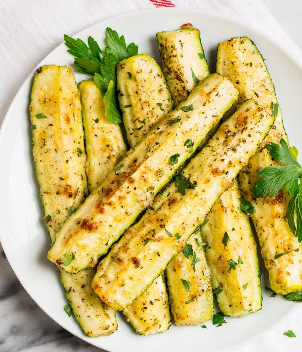 A plate of roasted zucchini that have been baked in the oven, topped with Parmesan and herbs