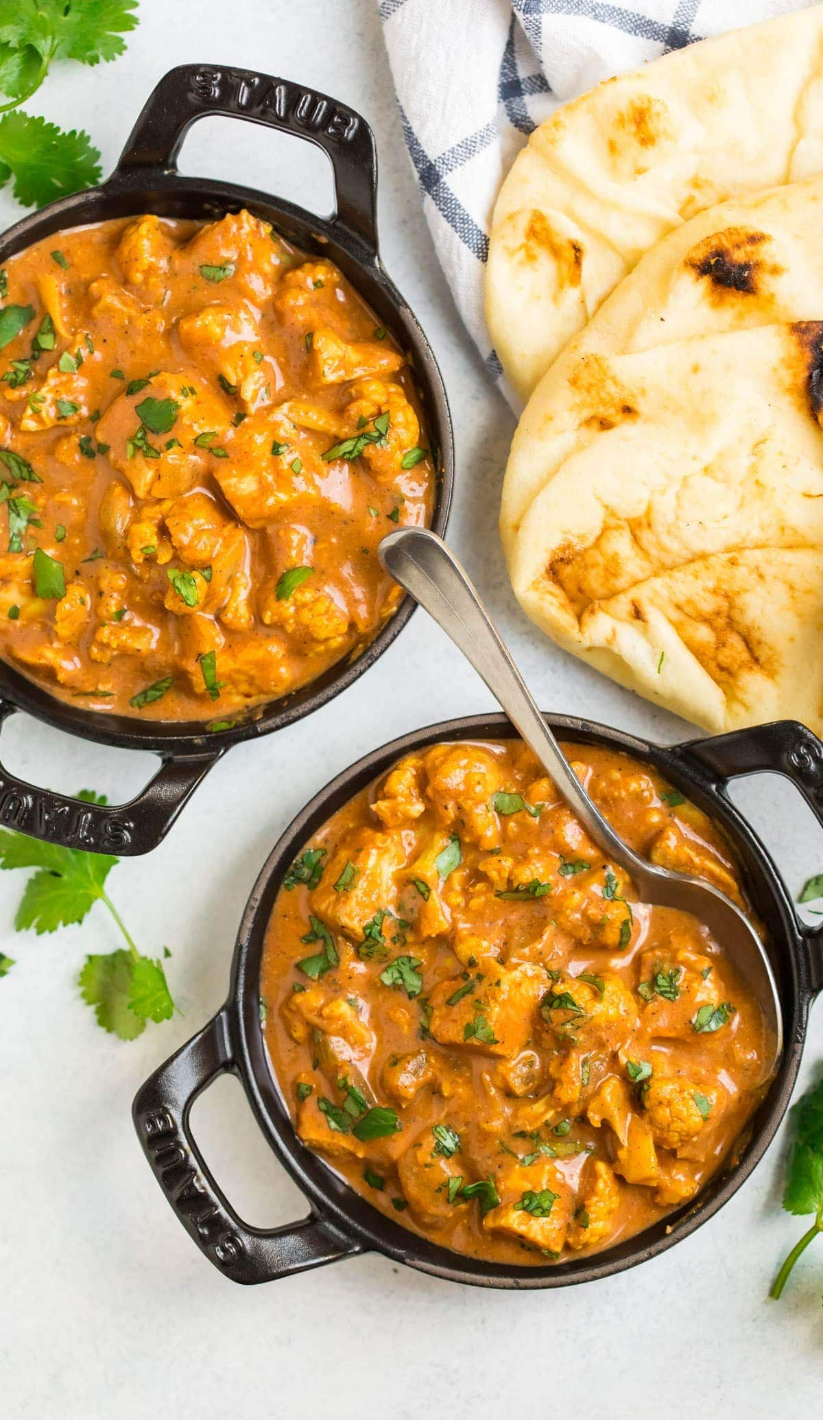 Two bowls of butter chicken with naan bread on the side