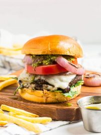 Cheese stuffed Portobello Mushroom Burger topped with pesto on a brown cutting board