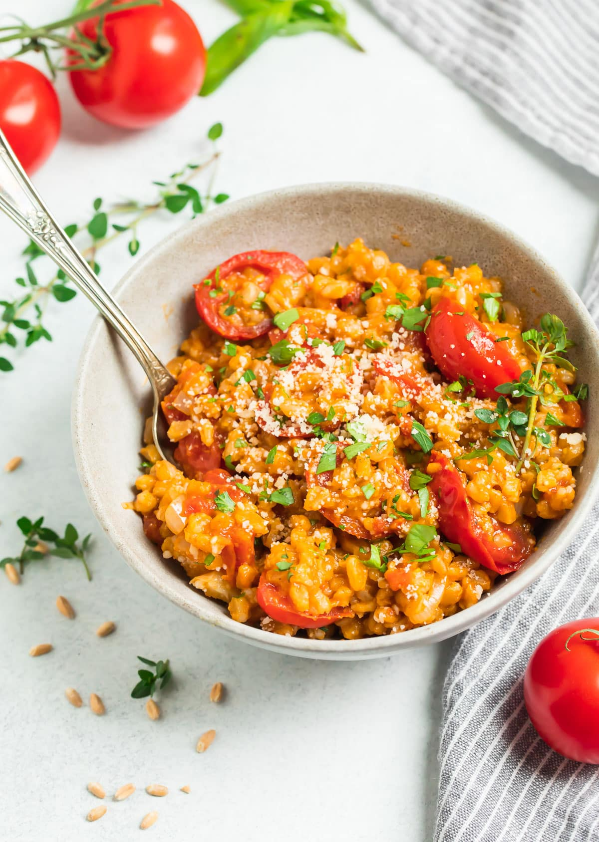 Tomato Farro Risotto garnished with herbs and Parmesan in a bowl with a spoon
