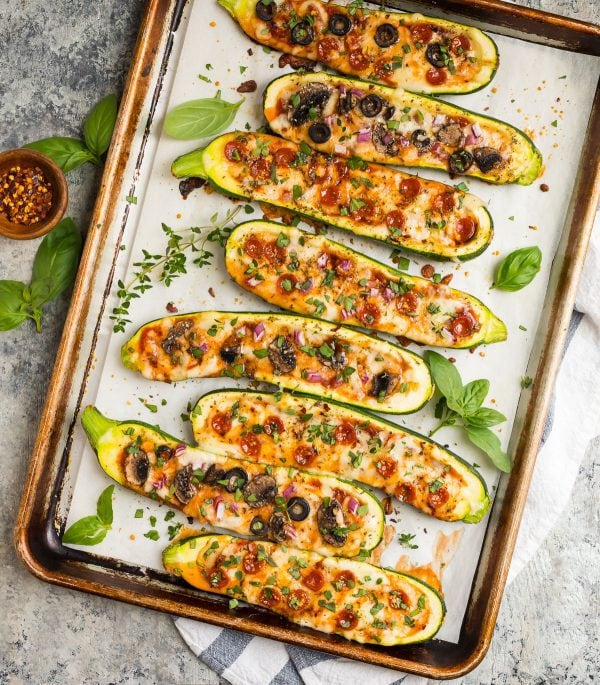 Golden brown Zucchini Pizza Boats on a sheet pan with herbs