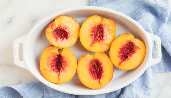 Sliced fresh peach halves in a white baking dish for making Baked Peaches.