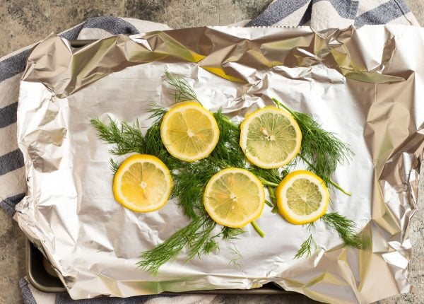 Fresh lemon slices and dill in foil to be topped with salmon for Grilled Salmon in Foil