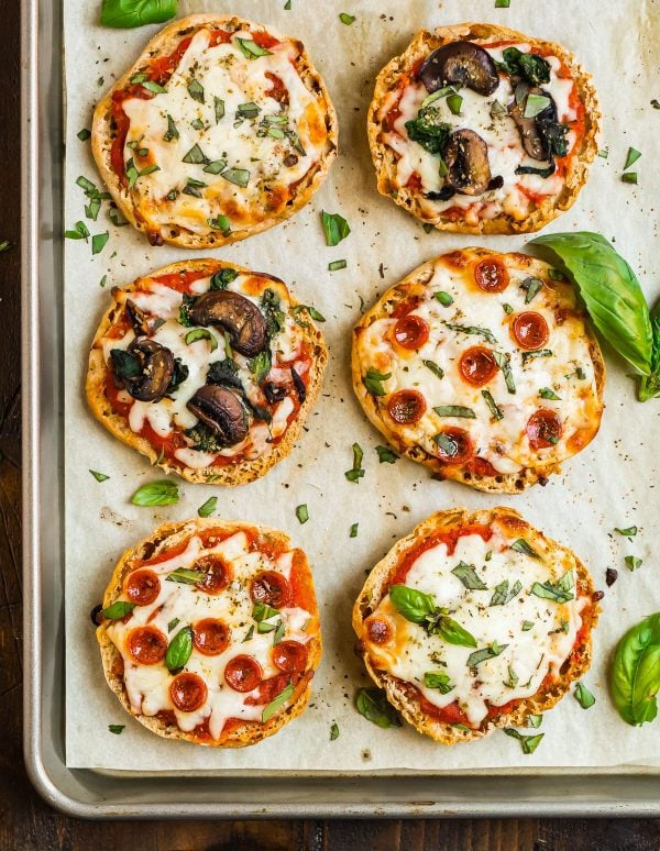 English Muffin Pizza baked in the oven for a not soggy crust and placed on a sheet pan with tomato sauce, pepperoni, vegetables, and fresh basil
