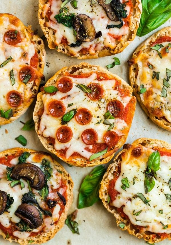 Healthy English Muffin Pizza baked in the oven for eating now or to make ahead and freeze for later placed on a sheet pan with tomato sauce, pepperoni, vegetables, and fresh basil