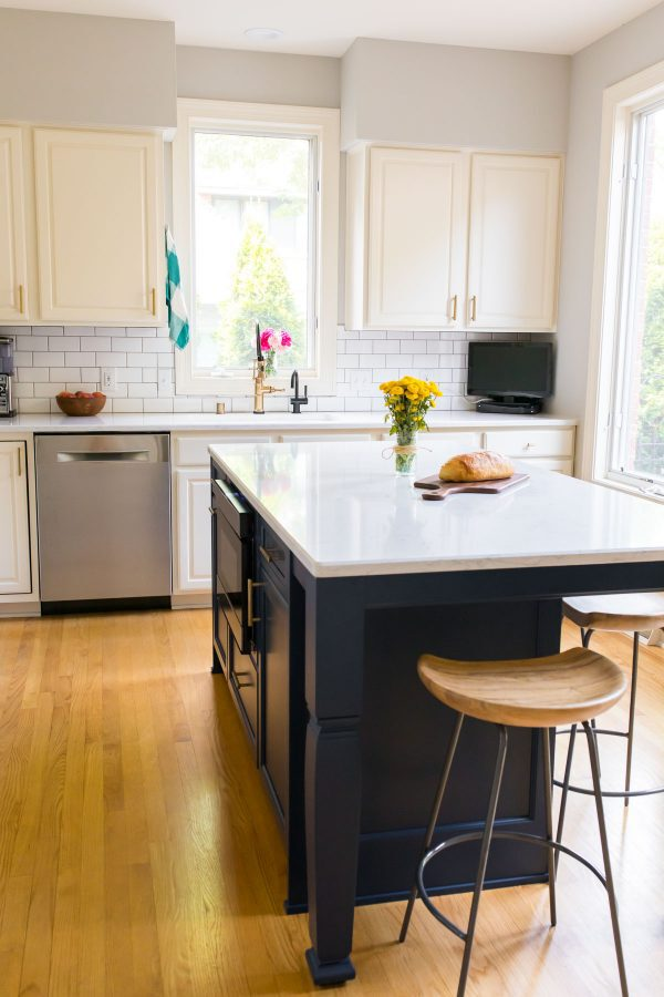 A bright, white kitchen with navy island and subway tile backsplash
