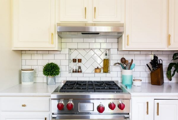 A stainless steel oven and gas cooktop in a kitchen with white cabinets