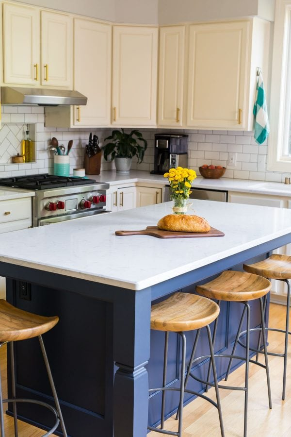 A kitchen with white cabinets, navy island, and subway tile backsplash