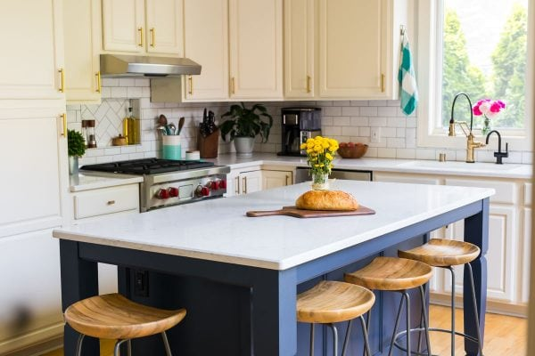 A navy island in a kitchen with white cabinets