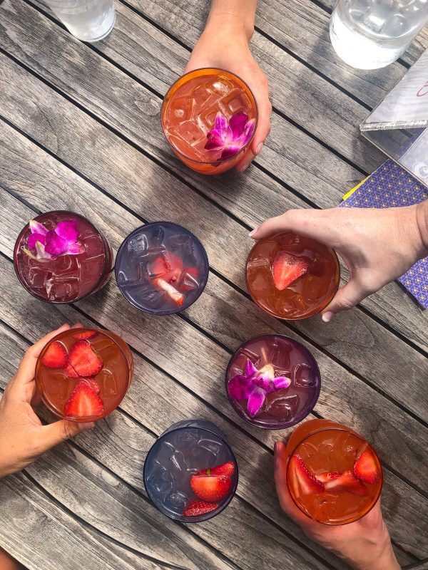 A group of colorful summer cocktails outside on a wooden table