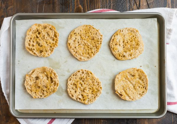 Healthy English Muffin Pizza toasting on a baking sheet for not soggy crust