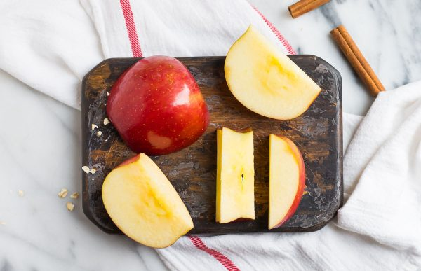 A sliced red apple on a cutting board