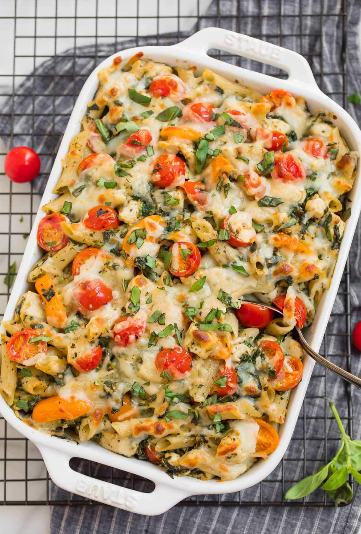 Tasty and creamy chicken pesto pasta recipe in a baking dish with tomatoes