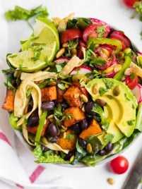 A healthy Mexican salad bowl with lettuce, beans, tomatoes, avocado and tortilla strips