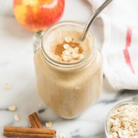 A mug with a creamy vegan apple smoothie with banana, oatmeal, and cinnamon