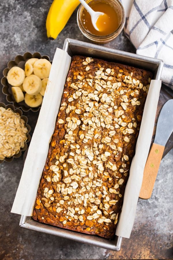 A loaf of oatmeal banana bread in a loaf pan with honey and bananas on the side