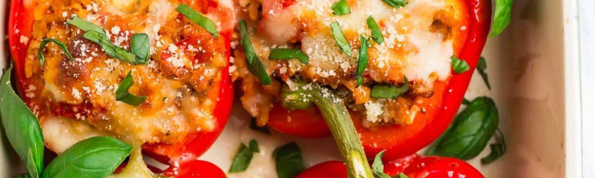 A pan of healthy Italian stuffed peppers; red bell peppers filled with ground chicken, tomatoes, and whole grains, then topped with basil and cheese.