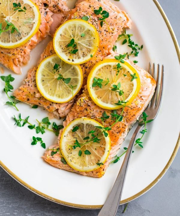 Perfectly cooked lemon pepper salmon with lemon slices and fresh herbs