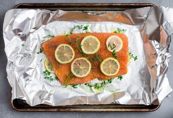 Lemon pepper salmon in aluminum foil with lemon and fresh herbs
