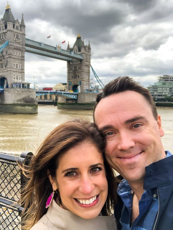 A man and woman photographed next to the Tower Bridge in London