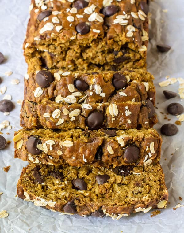 Slices of healthy pumpkin chocolate chip bread layers together on crinkled parchment paper