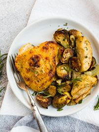 Golden and crispy rosemary chicken thighs with honey mustard apples and Brussels sprouts on a white plate with fresh rosemary on top.