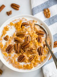 A bowl of easy healthy pumpkin oatmeal topped with pecans