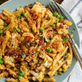 A blue plate with cauliflower pasta and bacon topping