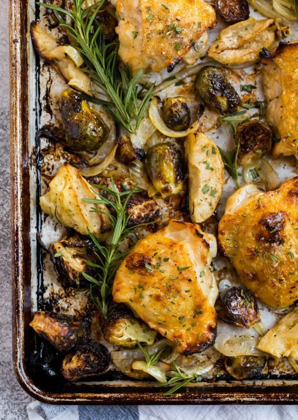 Crispy rosemary chicken thighs on a baking sheet with Brussels sprouts, onions, rosemary, and apples
