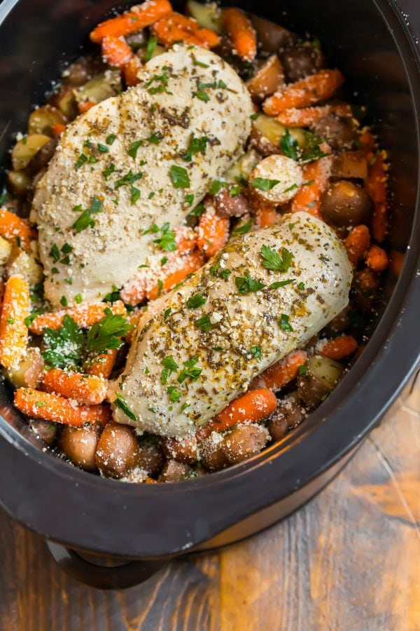 Deliciously easy crockpot chicken and potatoes in a slow cooker topped with fresh herbs and Parmesan cheese