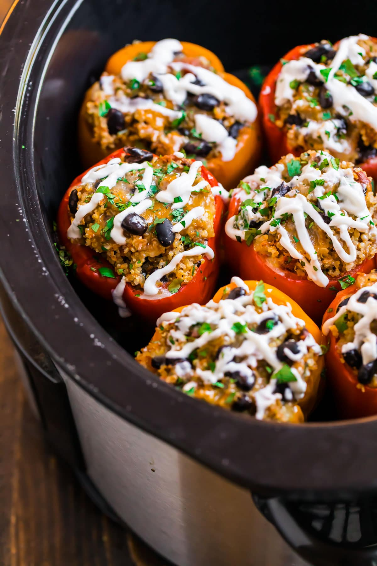 Healthy crockpot stuffed peppers in a slow cooker made with quinoa, black beans, ground chicken, and topped with cheese