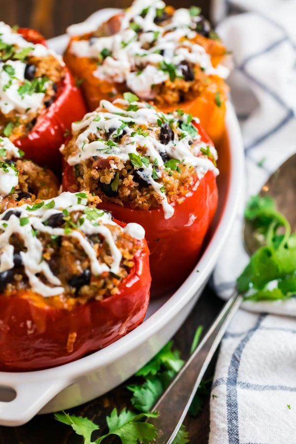 Healthy crockpot stuffed peppers with quinoa, black beans, and ground chicken served in a baking dish