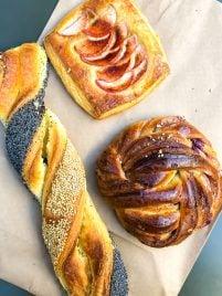 Danish pastries in Copenhagen, including a sesame braid, cinnamon bun, and apple croissant
