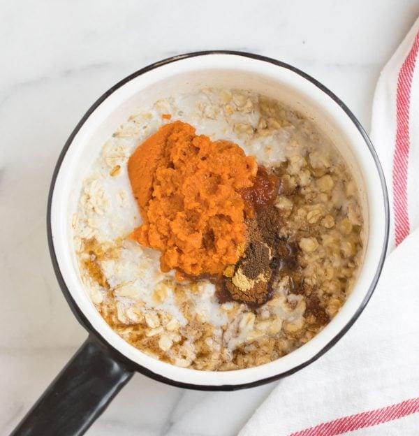 Almond milk, pumpkin puree, cinnamon, and oats in a mug for making healthy pumpkin oatmeal