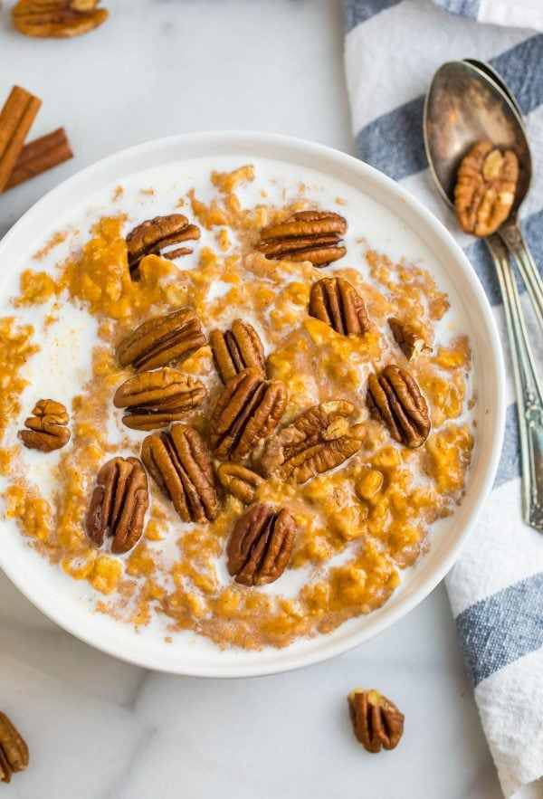 Healthy and tasty pumpkin oatmeal served in a bowl with pecans