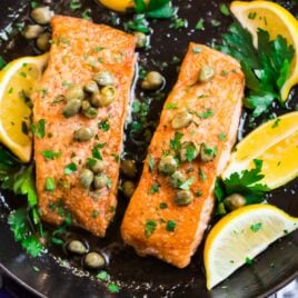 A skillet with two fillets of salmon meuniere with lemon, butter, and parsley