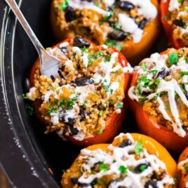Crockpot stuffed peppers in a slow cooker with a fork in one