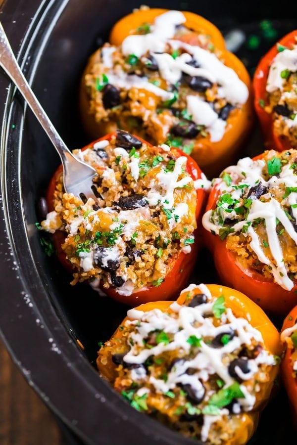 Healthy crockpot stuffed peppers with quinoa, ground chicken, black beans, and topped with cheese
