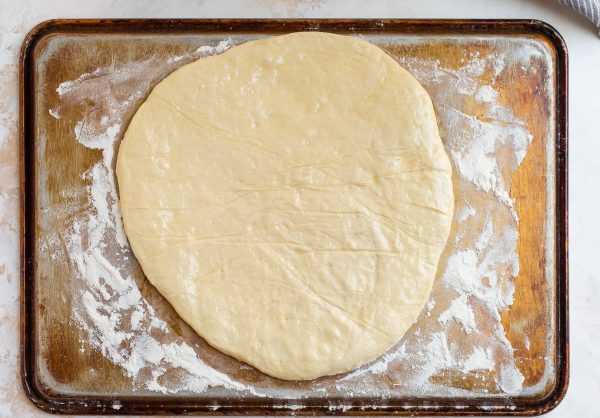 Circle of Pizza Dough on a Baking Sheet for Making Homemade Burrata Pizza