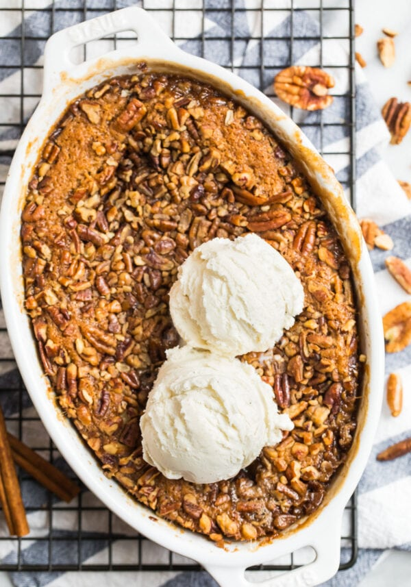 Pecan pie cobbler in a baking dish with two scoops ice cream