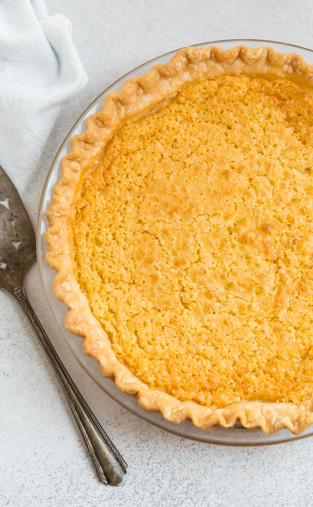 Old fashioned buttermilk pie with a flaky, buttery crust in a pie dish