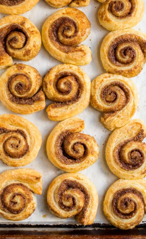 Tasty puff pastry cinnamon rolls on a baking sheet