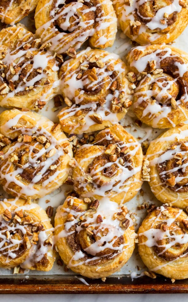 Tasty puff pastry cinnamon rolls with vanilla glaze and toasted pecans