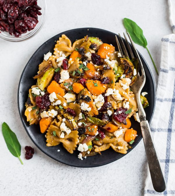 Easy sweet potato pasta with Brussels sprouts served on a plate with cranberries and cheese