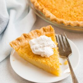 A slice of buttermilk pie on a white plate with whipped cream