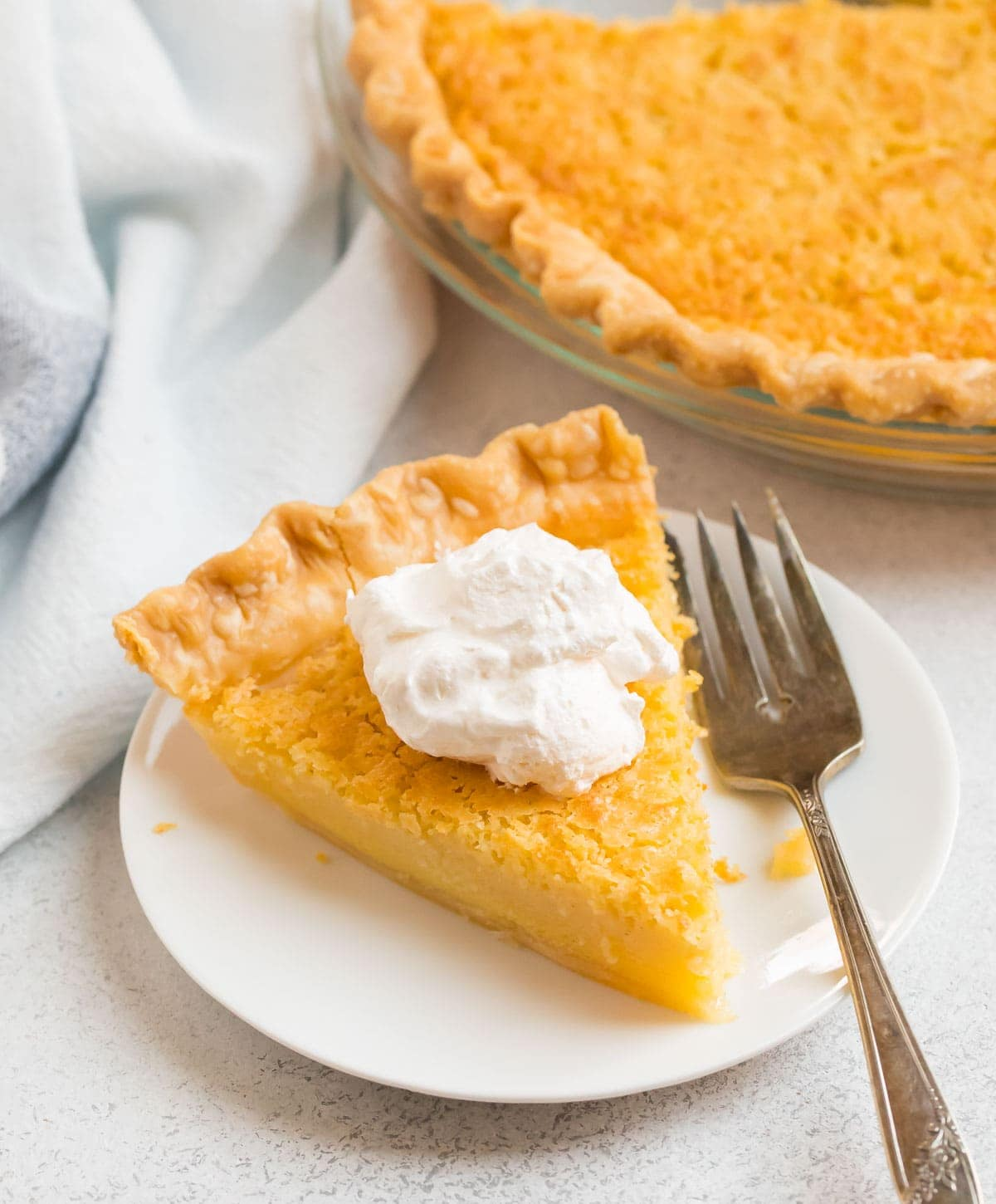A slice of old fashioned Buttermilk Pie with whipped cream on top