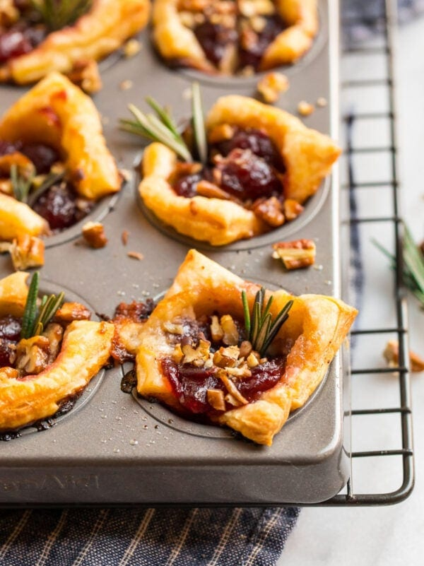 A mini muffin tin with cranberry brie bite appetizers, topped with pecans and rosemary springs