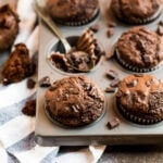 A muffin pan with moist chocolate muffins filled and topped with chocolate chunks